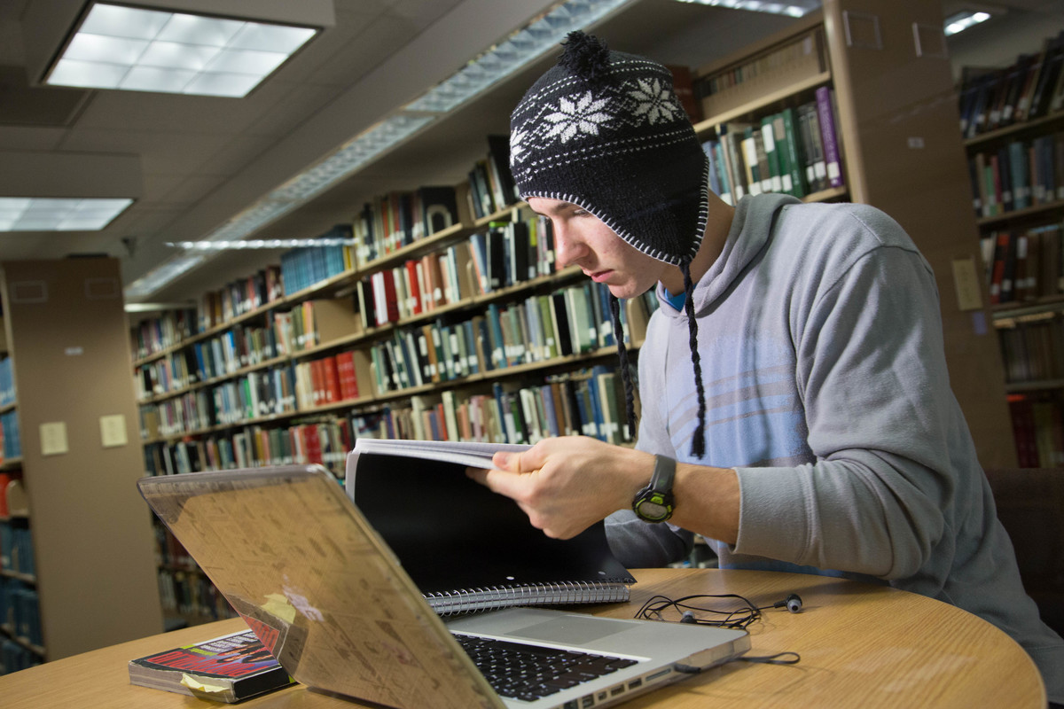 Student studying in the library, reading his notebook in front of laptop